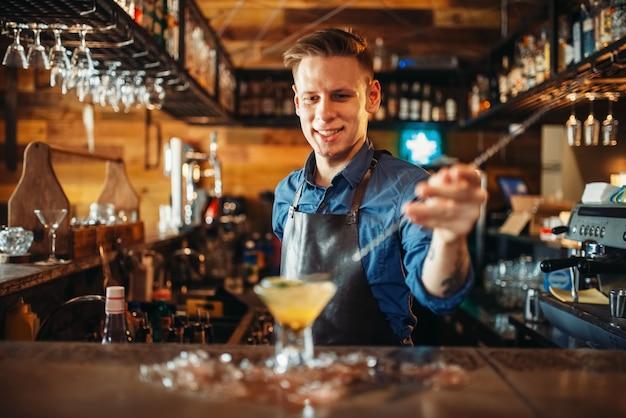 Mannelijke barman bereidt alcoholische cocktail met ijs