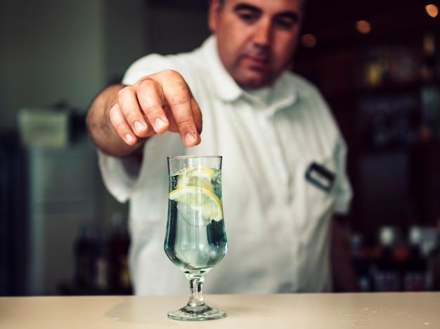 Mannelijke barman die duidelijke drank in glas bevestigt