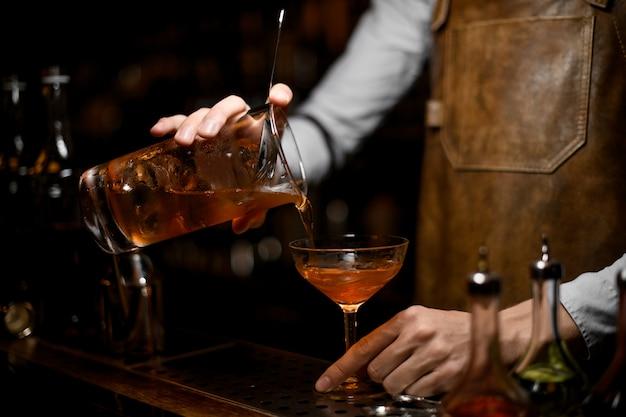Mannelijke barman die een bruine alcoholische drank van de maatbeker gieten naar het cocktailglas