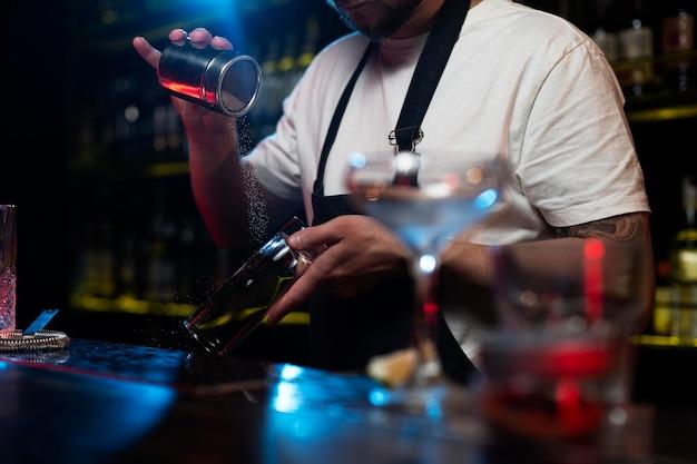 Mannelijke barman die een cocktail maakt met een shaker