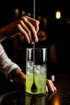 Mannelijke barman die een cocktail voorbereidt, een groene drank in een het mengen glas met een staaflepel roert