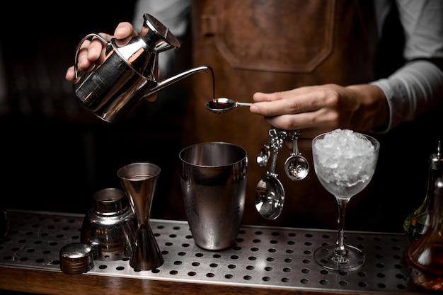 Mannelijke barman die een essentie van de staalketel giet aan de lepel