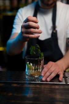 Mannelijke barman die een heerlijke cocktail maakt