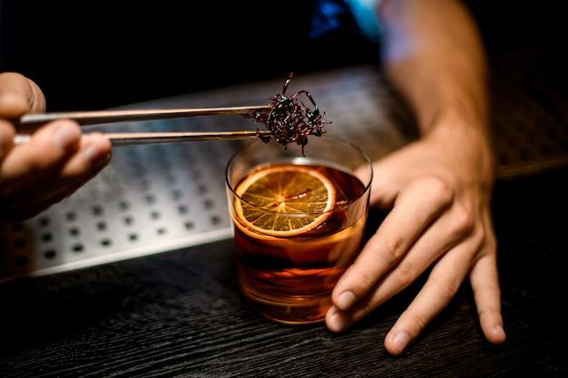 Mannelijke barman die gekoelde bruine karamel met twezzers aan de cocktail met ijsblokjes en gedroogde sinaasappelplak toevoegen