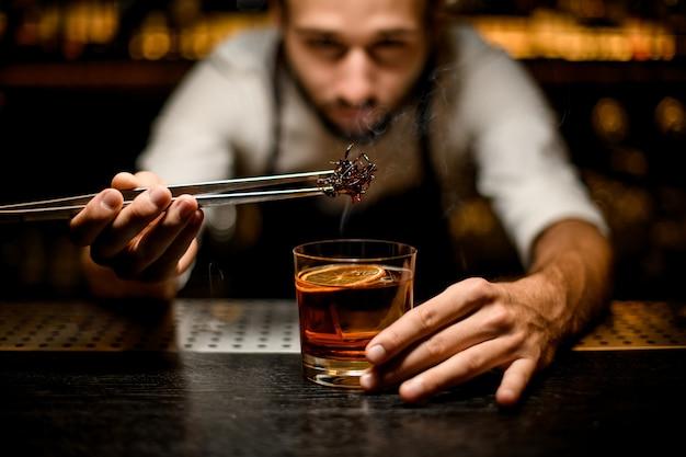 Mannelijke barman die gekoelde bruine karamel met twezzers toevoegen aan de cocktail met ijsblokjes