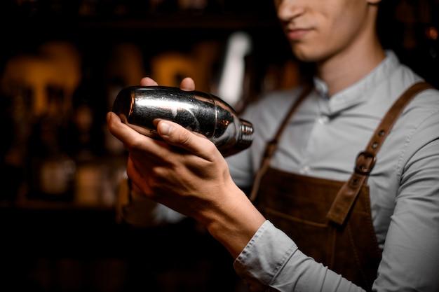 Mannelijke barman die in handen een staalschudbeker houdt