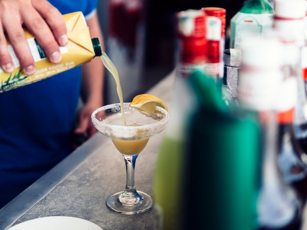 Mannelijke barman die kleurrijke drank met sap maakt