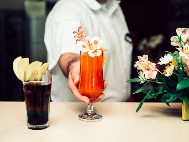 Mannelijke barman die kleurrijke verfraaide drank dient