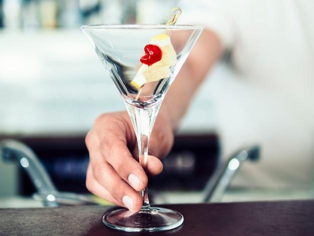 Mannelijke barman dienende cocktail met fruit