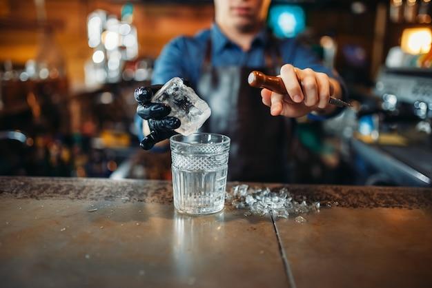 Mannelijke barman giet een drankje in een glas met ijs