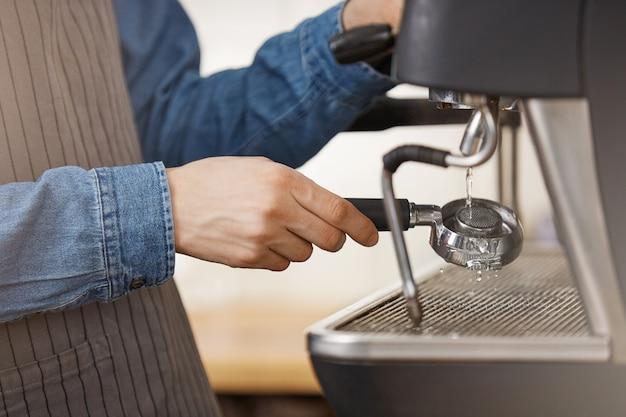 Mannelijke barman in denim overhemd en schort schoonmaken bodemloze filterdrager.