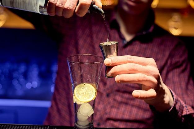 Mannelijke barman in een nachtclub op het werk, voorbereiding van een cocktail in een groot glas.