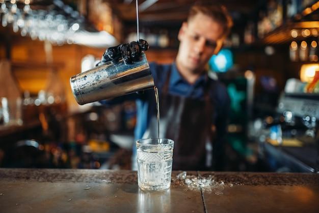 Mannelijke barman in schort giet een drankje in een glas