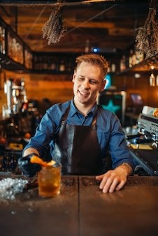 Mannelijke barman in schort werkt aan de toog