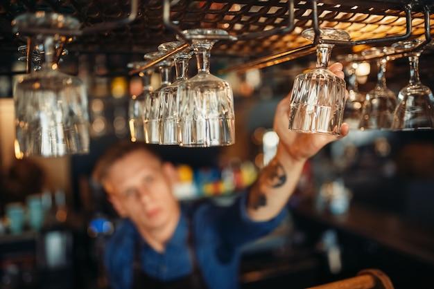 Mannelijke barman neemt schoon glas van toog
