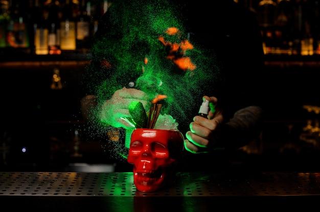 Mannelijke barman sproeit op de cocktail in de rode scull-beker van de verdamper en vlamt het in het groene licht op de toog