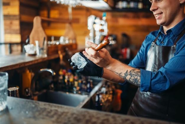 Mannelijke barman steekt ijs aan de toog