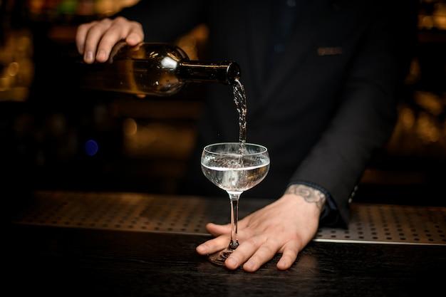 Mannelijke barman voegt champagne in een glas toe