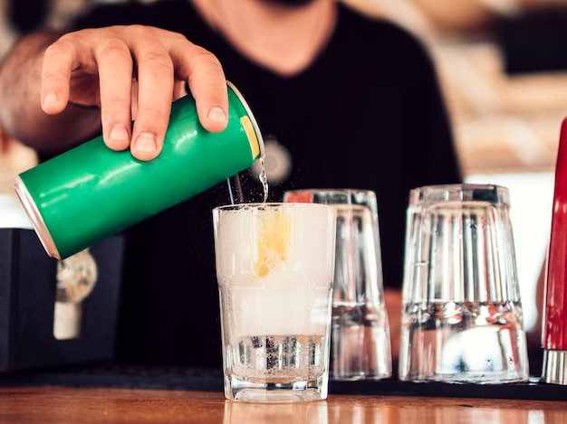 Mannelijke bartender gieten soda in cocktail