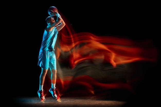Mannelijke basketbalspeler die basketbal speelt geïsoleerd over donkere studiomuur in gemengd licht.