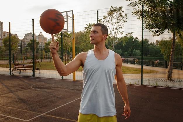 Mannelijke basketbalspeler die de bal op zijn vinger op buitenhof spint