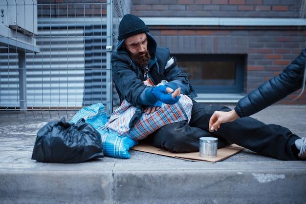 Mannelijke bebaarde bedelaar bedelen op straat in de stad.
