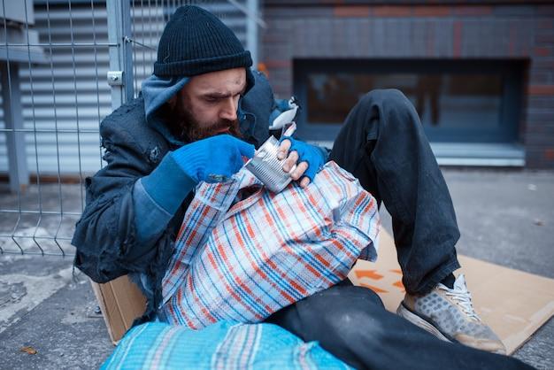 Mannelijke bebaarde bedelaar eet op straat.
