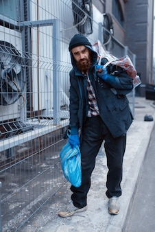 Mannelijke bebaarde bedelaar met tas op straat in de stad.