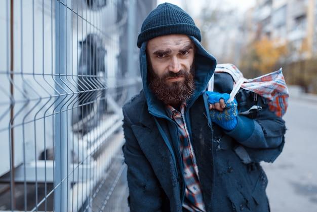 Mannelijke bebaarde bedelaar met tas op straat.