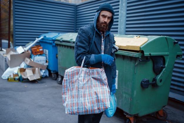 Mannelijke bebaarde bedelaar op zoek naar voedsel in de prullenbak op straat.