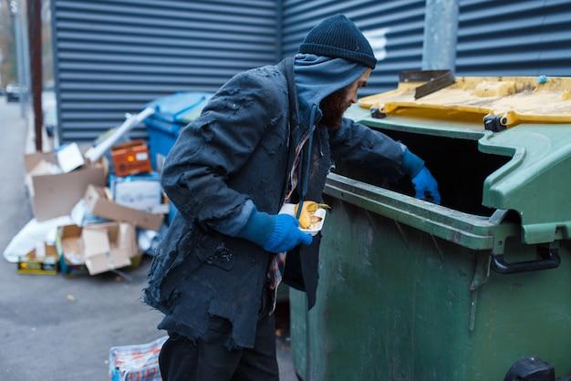 Mannelijke bebaarde bedelaar voedsel zoeken in prullenbak