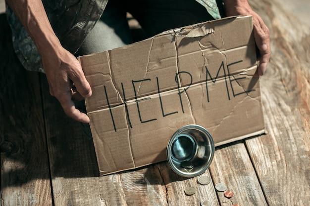Mannelijke bedelaarshanden die geld zoeken met het bord help me van menselijke vriendelijkheid op de houten vloer op het openbare pad of straatpad. dakloze armen in de stad. problemen met financiën, woonplaats.