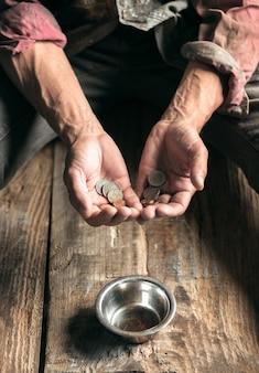 Mannelijke bedelaarshanden op zoek naar geld, munten van menselijke vriendelijkheid op de houten vloer op het openbare pad of straatpad. dakloze armen in de stad. problemen met financiën, woonplaats.