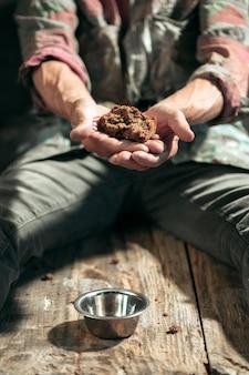 Mannelijke bedelaarshanden op zoek naar voedsel of geld met muntenblikje van menselijke vriendelijkheid