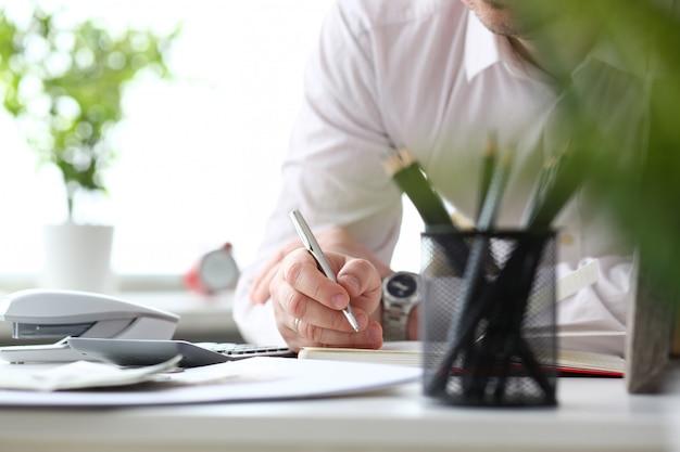 Mannelijke bediendehand die zilveren pen houden die iets schrijven