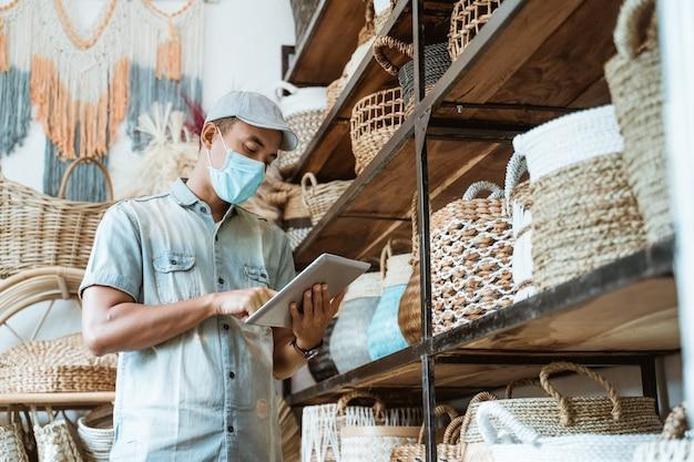 Mannelijke bedrijfseigenaar draagt gezichtsmaskers in zijn kunst- en ambachtswinkel