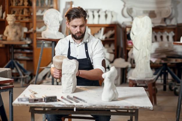 Mannelijke beeldhouwer in wit overhemd en zwarte schort maakt een kalkstenen kopie van vrouwentorso in de artistieke studio.