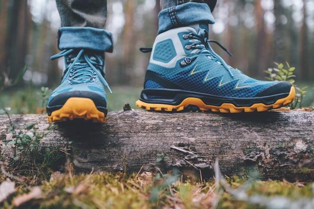 Mannelijke benen dragen sportieve wandelschoenen. herenbenen in trekkingschoenen voor buitenactiviteiten.