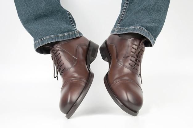 Mannelijke benen in jeans en bruine klassieke schoenen op witte achtergrond. leer modieuze schoenen voor heren