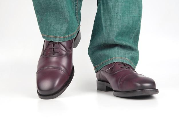 Mannelijke benen in jeans en bruine klassieke schoenen op witte achtergrond