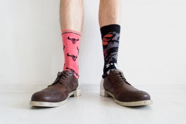 Mannelijke benen in niet-overeenkomende sokken die bruine schoenen over witte achtergrond dragen.