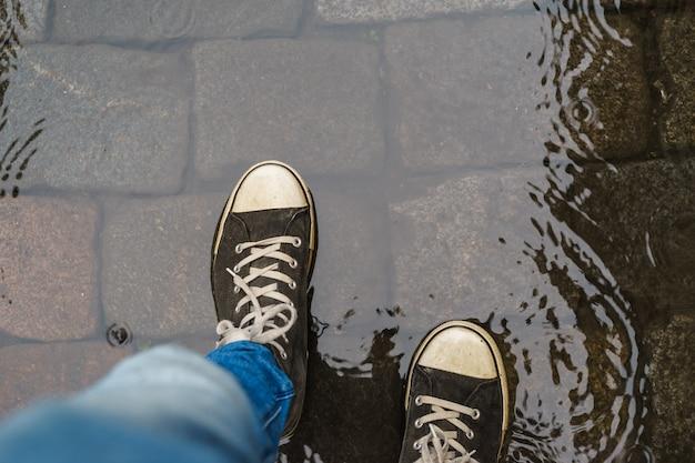 Mannelijke benen in sneakers lopen door regen plas