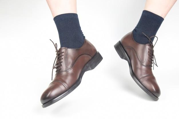 Mannelijke benen in sokken en bruine klassieke leren schoenen op een witte achtergrond