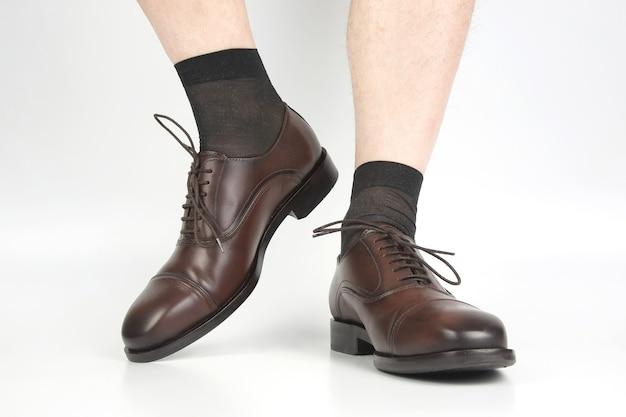 Mannelijke benen in sokken en bruine klassieke schoenen op een wit