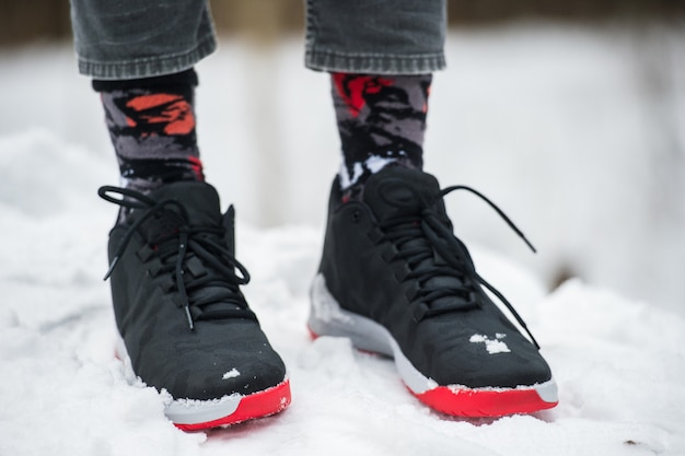 Mannelijke benen in sportschoenen, cropped jeans en modieuze sokken staande op sneeuw.