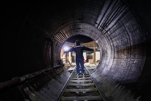 Mannelijke beperkte ondergrondse tunnel van verwarmingskanaal met roestige buizen en rail