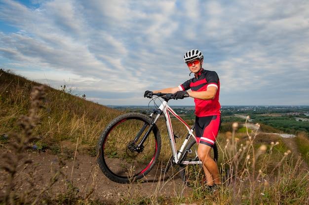 Mannelijke bergfietser in rode sportkleding die dichtbij zijn fiets rusten