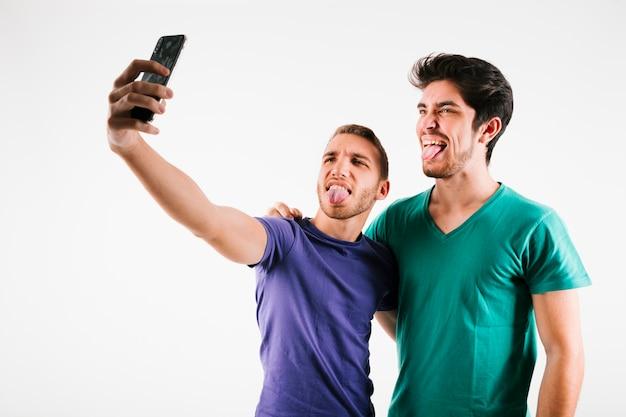 Mannelijke beste vrienden nemen selfie en grimassen