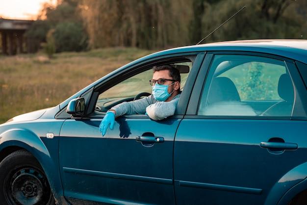 Mannelijke bestuurder die beschermende handschoenen en masker draagt