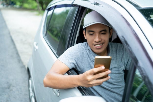 Mannelijke bestuurder gebruikt een smartphone voor vertrek
